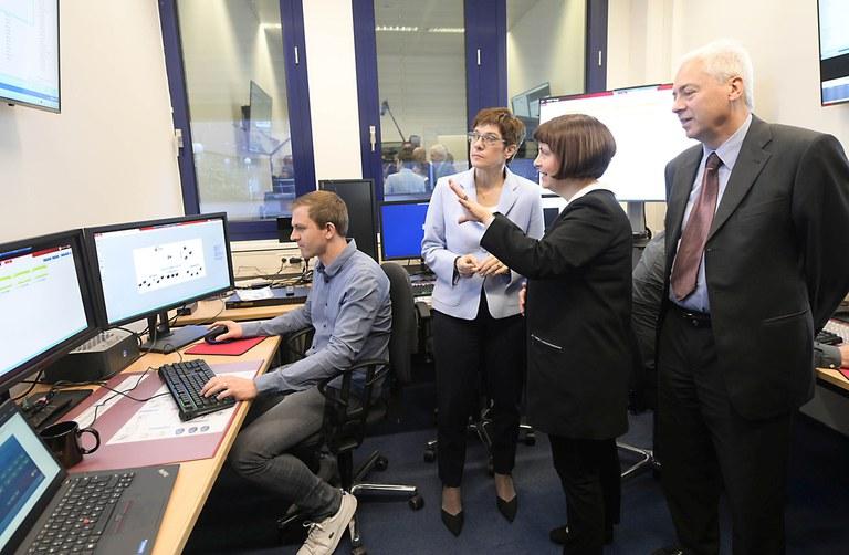 Ein Mitarbeiter von Code sitzt an einem Schreibtisch vor drei Monitoren, hinter ihm steht die Ministerin und blickt auf einen der Monitore, neben ihr steht Professorin Dreo und erläutert etwas, neben Professorin Dreo steht Professor Buchenrieder