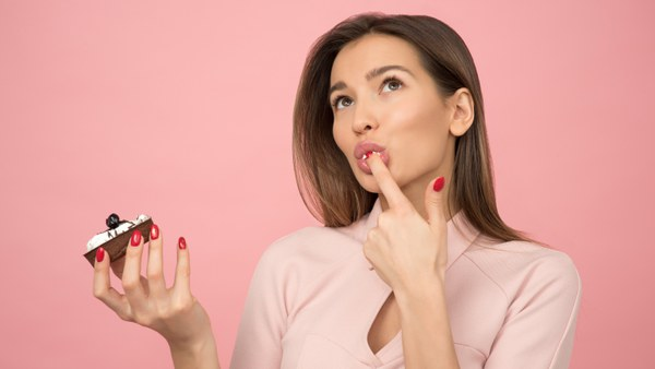 woman-eating-cupcake-while-standing-near-pink-background-1036621.jpg