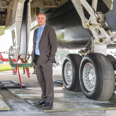 Professor Stütz unter einem Flugzeug.